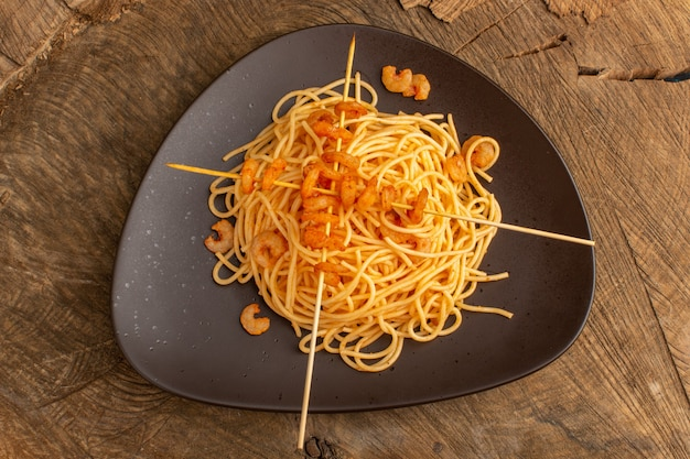 Draufsicht auf gekochte italienische nudeln mit garnelen innerhalb der braunen platte auf der holzoberfläche Kostenlose Fotos