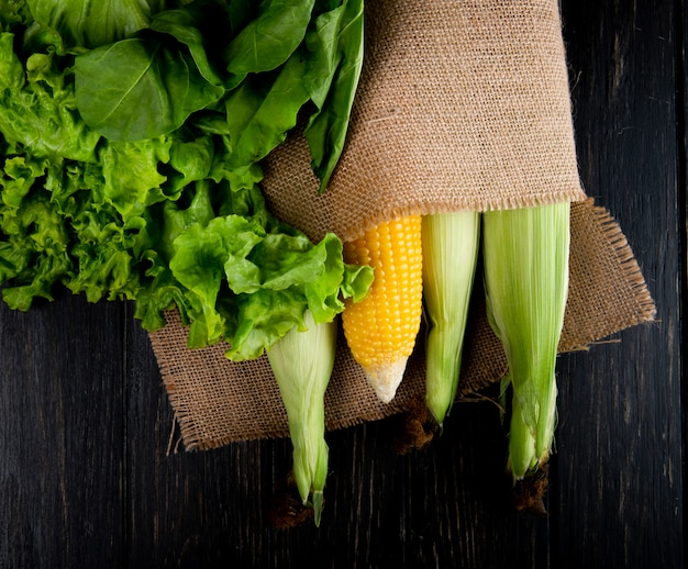 Draufsicht auf gekochte und ungekochte körner im sack mit salat und spinat auf schwarz Kostenlose Fotos