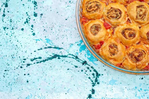 Draufsicht auf gekochtes teigmehl mit hackfleisch und tomatensauce in der glaspfanne auf hellblauem schreibtisch, das backen von fleischteigfarbe kocht Kostenlose Fotos