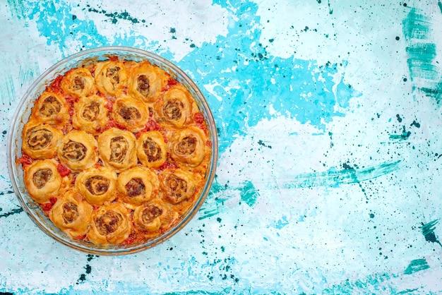 Draufsicht auf gekochtes teigmehl mit hackfleisch und tomatensauce in glaspfanne auf hellblauem schreibtisch, backen von fleischteig kochen Kostenlose Fotos