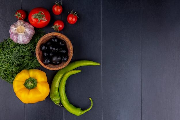 Draufsicht auf gemüse als schüssel olivenpfeffer-tomaten-knoblauch-dill auf schwarzer oberfläche Kostenlose Fotos