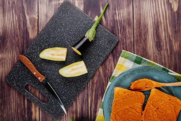 Draufsicht auf geschnittene auberginen und küchenmesser an bord zum kochen und toasten mit auberginenkaviar Kostenlose Fotos