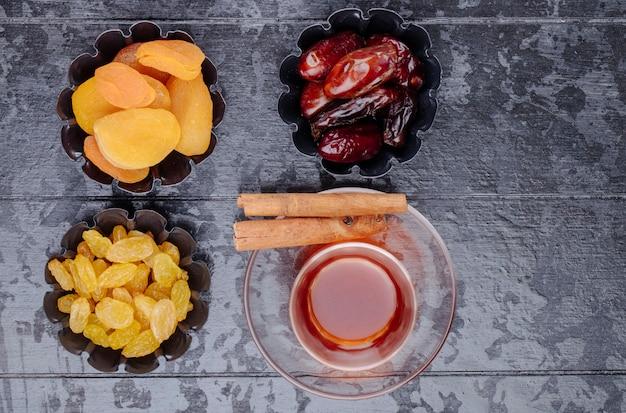 Draufsicht auf getrocknete früchte rosinen aprikosen und getrocknete datteln in mini-torten-dosen serviert mit tee auf schwarzem holzhintergrund Kostenlose Fotos