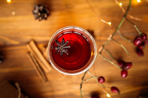 Draufsicht auf glasbecher schwarzen tees mit sternanis auf dem hölzernen festlichen tisch Premium Fotos