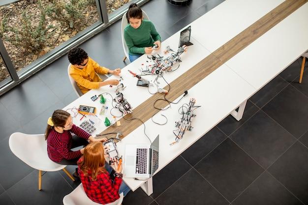 Draufsicht auf gruppe der glücklichen kinder, die elektrisches spielzeug und roboter am robotikklassenzimmer programmieren Premium Fotos