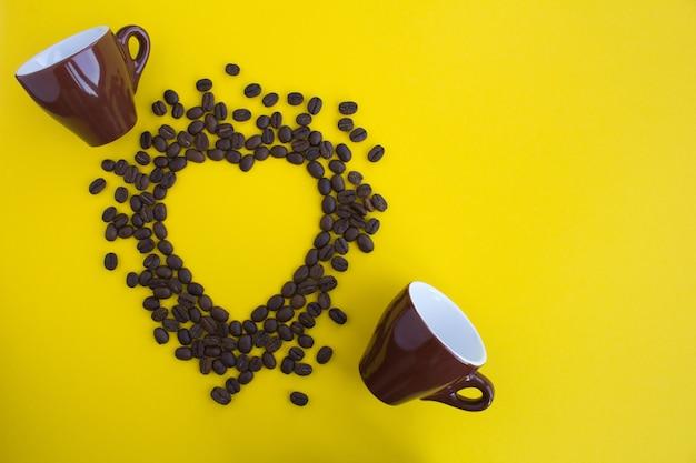 Draufsicht auf kaffeebohnen in form von hitze und zwei browncups Premium Fotos