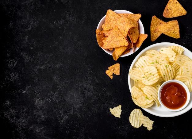 Draufsicht auf kartoffelchips und nacho-chips mit ketchup Kostenlose Fotos