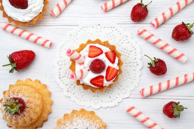 Draufsicht auf kleine leckere kuchen mit sahne und geschnittenen erdbeersüßigkeiten auf weiß Kostenlose Fotos
