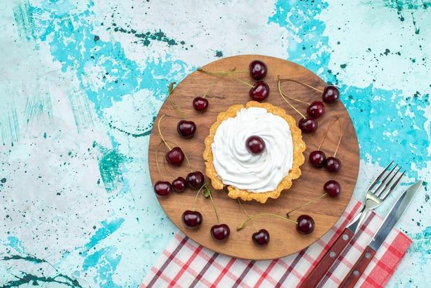 Draufsicht auf kleinen kuchen mit sahne und frischkirschen auf hellblauem, fruchtfrischem kuchenkeks süß Kostenlose Fotos