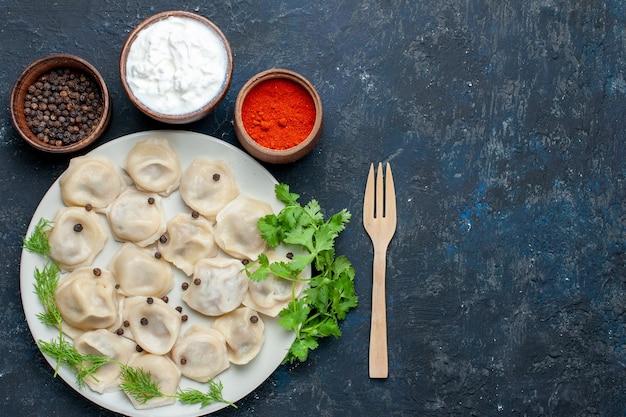 Draufsicht auf köstliche gebackene knödel innerhalb des tellers zusammen mit joghurt und grün auf dunkelgrauem, teigabendessenfleischkalorienmahlzeitnahrung Kostenlose Fotos