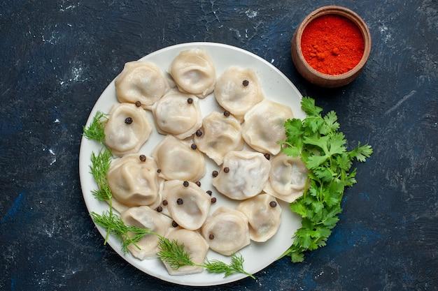 Draufsicht auf köstliche gebackene knödel innerhalb platte zusammen mit pfeffer und grün auf grauem schreibtisch, teigmahlzeit abendessen fleischkalorie Kostenlose Fotos