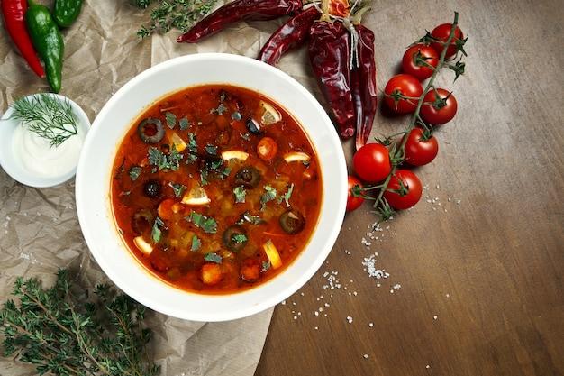 Draufsicht auf leckere solyanka dicke, würzige und saure russische suppe mit oliven, zitrone und würstchen in weißer schüssel auf holzoberfläche. Premium Fotos