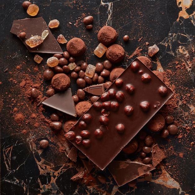 Draufsicht auf luxuriöse köstliche schokoladen- und bonbontrüffel in kakaopulver auf der marmoroberfläche Premium Fotos