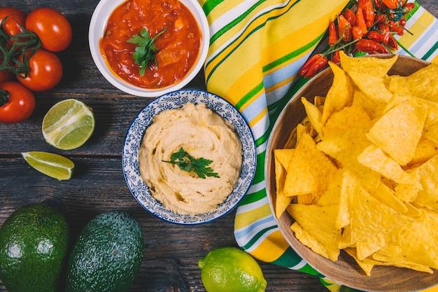 Draufsicht auf mexikanische nachos-chips; avocado; salsa-sauce; kirschtomaten; rote chilischoten und zitrone auf dem tisch Kostenlose Fotos