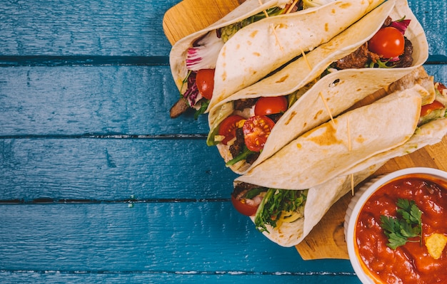 Draufsicht auf mexikanische tacos; salsasauce mit fleisch und gemüse auf schneidebrett Kostenlose Fotos