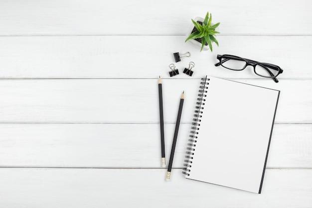 Draufsicht auf minimalen schreibtisch mit offenem leerem notizbuch und schreibwaren Premium Fotos