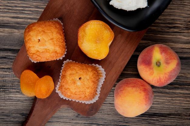 Draufsicht auf muffins mit getrockneten aprikosen auf holzschneidebrett und frischen pfirsichen auf rustikalem Kostenlose Fotos
