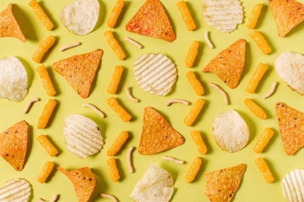 Draufsicht auf nacho-chips mit kartoffelchips und käsigen hauchen Kostenlose Fotos
