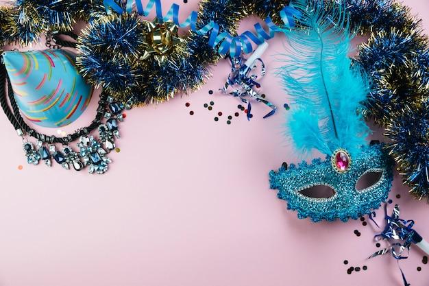 Draufsicht auf partyhut; lametta; halskette mit konfetti und blauer maskerade-karnevalsfedermaske Kostenlose Fotos
