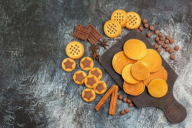 Draufsicht auf pfannkuchen auf holzplatte mit keksen und süßigkeiten auf grauem grund Kostenlose Fotos