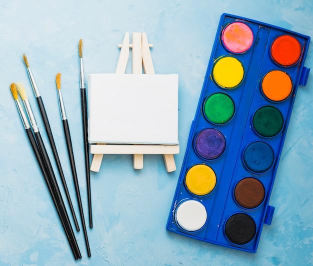 Draufsicht auf pinsel; mini-staffelei und aquarell-palette Kostenlose Fotos