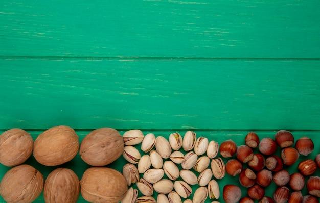 Draufsicht auf pistazien mit haselnüssen und walnüssen auf einer grünen oberfläche Kostenlose Fotos