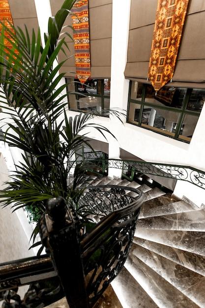 Draufsicht auf restauranttreppen aus schwarzem marmor und langen fenstern mit stoffjalousien Kostenlose Fotos