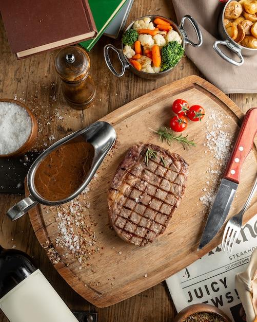 Draufsicht auf rindersteak serviert mit sauce und gekochtem gemüse Kostenlose Fotos