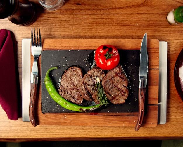 Draufsicht auf rindfleischsteaks, die mit gegrillter tomate und pfeffer serviert werden Kostenlose Fotos