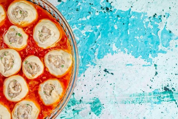 Draufsicht auf rohe fleischige teigteigscheiben mit hackfleisch innen mit tomatensauce in glaspfanne auf blauem schreibtisch Kostenlose Fotos