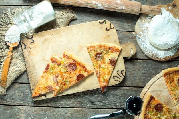 Draufsicht auf scheiben pizzasalami mit tomatensauce grünem chili-pfeffer und gewürzen Kostenlose Fotos