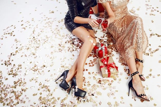 Draufsicht auf sexy frauenbeine auf hintergrund des glänzenden goldenen konfettis, geschenkboxen, gläser champagner. glitzerndes abendkleid tragen. zeit feiern. Kostenlose Fotos