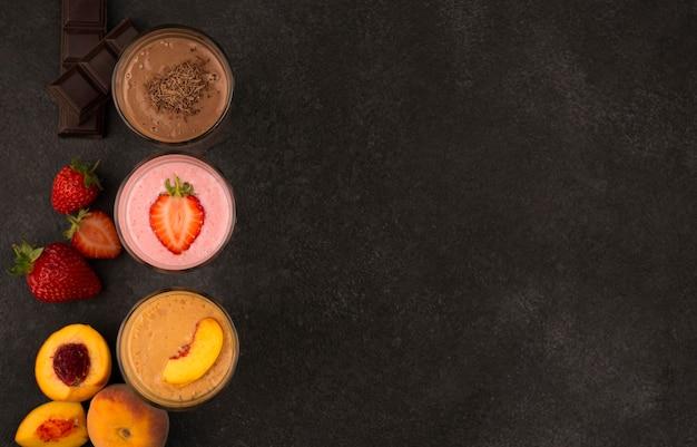 Draufsicht auf sortiment von milchshakes mit früchten und schokolade mit kopienraum Premium Fotos
