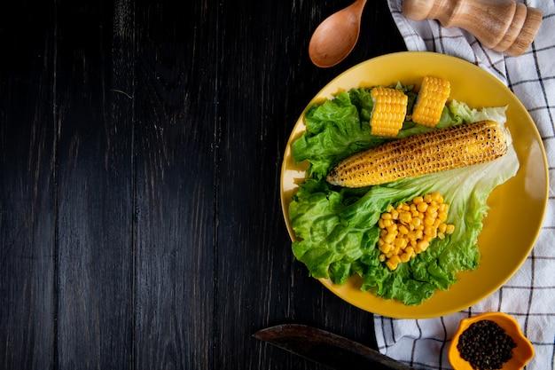 Draufsicht auf teller des ganzen und geschnittene körner mit maissamen und salat mit messer auf stoff und schwarz mit kopierraum Kostenlose Fotos