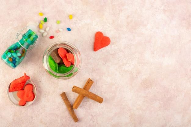 Draufsicht auf verschiedene kekse süß und lecker mit zimt und süßigkeiten auf der rosa oberfläche Kostenlose Fotos