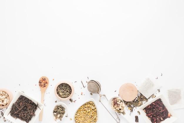 Draufsicht auf verschiedene kräuter; löffel; teesieb; trockene teeblätter angeordnet auf weißem hintergrund Kostenlose Fotos