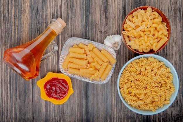 Draufsicht auf verschiedene makkaronis als ziti rotini und andere mit knoblauch geschmolzener butter und ketchup auf holz Kostenlose Fotos