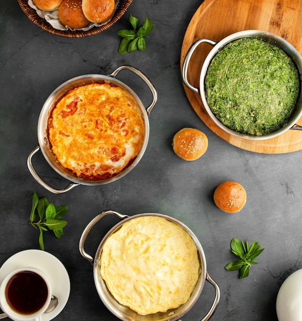 Draufsicht auf verschiedene spiegeleifrühstückseier mit klassischem tomatenomelett und aserbaidschanischem kuku auf schwarzem Kostenlose Fotos