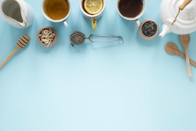 Draufsicht auf verschiedene teesorten; honigschöpflöffel; sieb; trockene teeblätter; teekanne auf blauem hintergrund Kostenlose Fotos