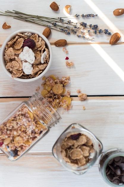 Draufsicht auf verschüttetes müsliglas in der nähe von cornflakes; trockenfrüchte und schokoladenstückchen auf holzoberfläche Kostenlose Fotos
