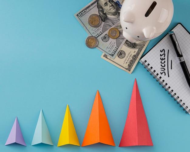 Draufsicht auf wachstumskegel mit banknoten und sparschwein Kostenlose Fotos