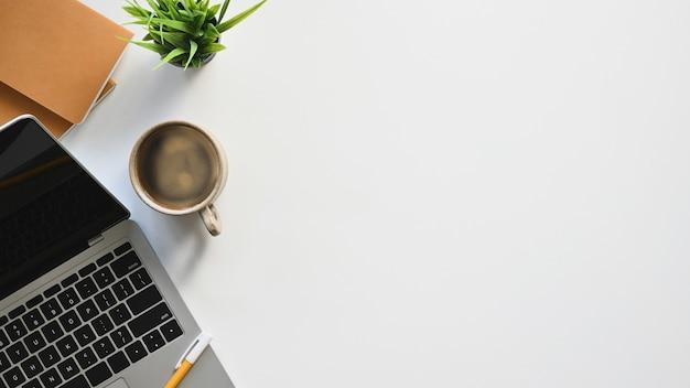 Draufsicht auf weißen schreibtisch mit zubehör computer-laptop, kaffeetasse, topfpflanze und notizbuch. Premium Fotos