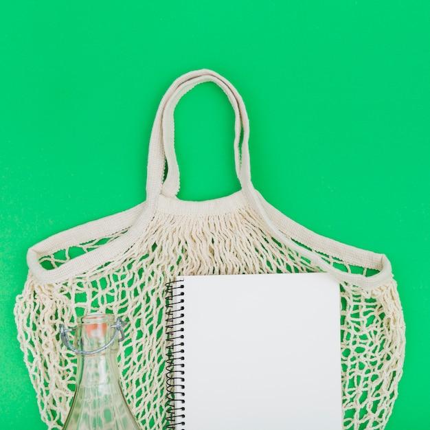 Draufsicht auf wiederverwendbare tasche mit notizbuch und glasflasche Kostenlose Fotos