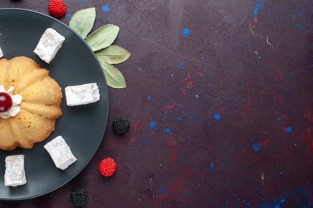 Draufsicht auf zuckerpulverbonbons köstliches nougat mit kuchen und konfektionsbeeren auf dunkler oberfläche Kostenlose Fotos