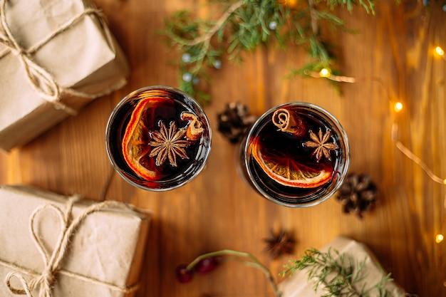 Draufsicht auf zwei glasbecher glintwine mit bastelgeschenken und girlandenlichtern auf dem holztisch Premium Fotos
