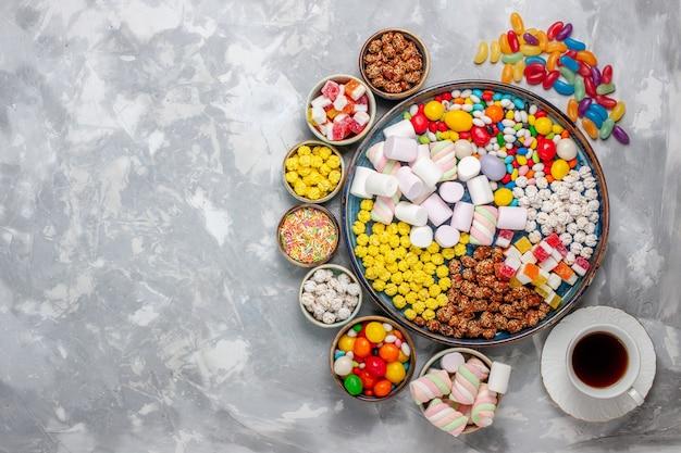 Draufsicht bonbon zusammensetzung verschiedenfarbige bonbons mit marshmallow und tee auf weißen schreibtisch zucker bonbon bonbon süße confitures Kostenlose Fotos