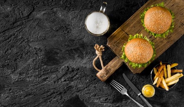 Draufsicht burger und pommes mit bier und kopierraum Kostenlose Fotos