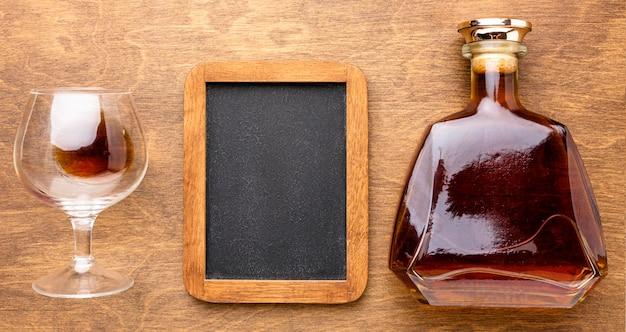 Draufsicht cognacflasche und glas mit leerem schwarzboot Kostenlose Fotos
