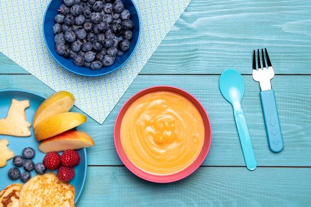 Draufsicht der babynahrung mit schüssel blaubeeren und früchten Kostenlose Fotos