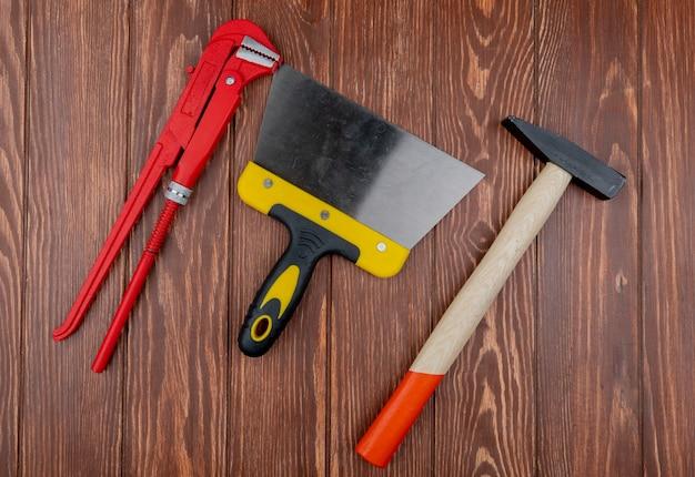 Draufsicht der bauwerkzeuge als schlüsselkittmesser und ziegelhammer auf hölzernem hintergrund Kostenlose Fotos